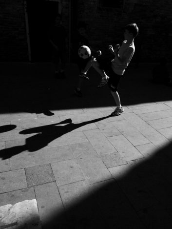 Young boy playing soccer in the street